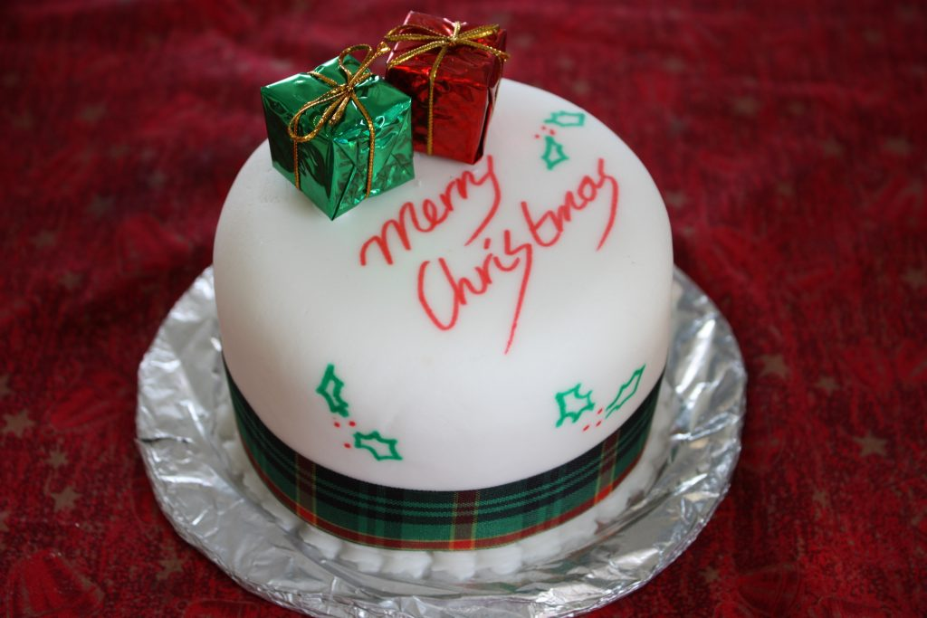 "Xmas cake with two present above it and a ""Merry Christmas"" text on it"