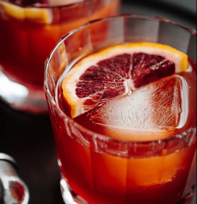 Xalapa Punch is served in a whiskey glass with a slice of blood orange and ice