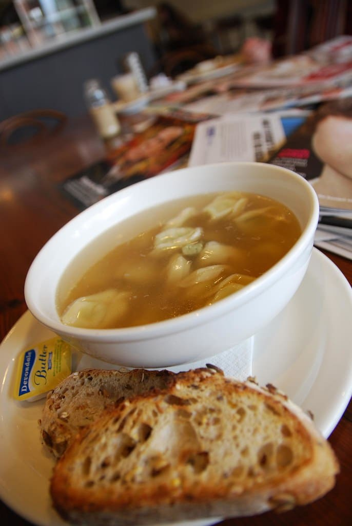 Xavier Soup in a white plate served with full-grain bread. Xavier is one of the foods that start with X
